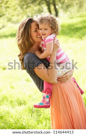 Mother Carrying Young Daughter Through Summer Field