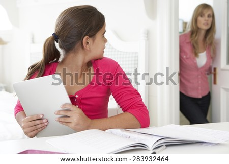 Mother Catches Daughter Using Tablet Computer When Meant To Be Studying - stock photo
