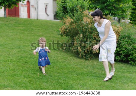 mother catching her running daughter - stock photo