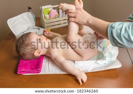 Mother changing diaper of adorable baby with a hygiene set for babies on the background - stock photo