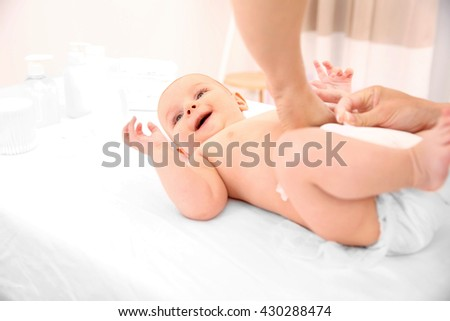 Mother changing diaper to little baby in room