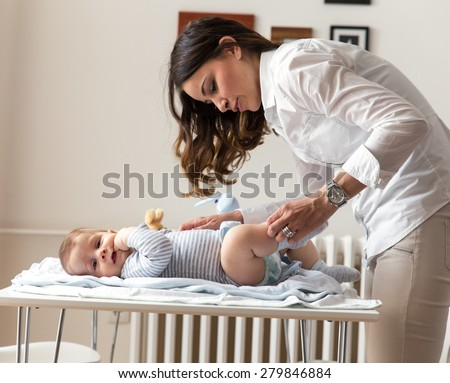 Mother changing her baby diapers. - stock photo