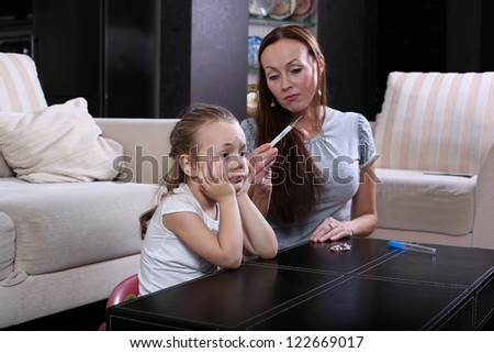 mother checking the temperature  her sick  daughter