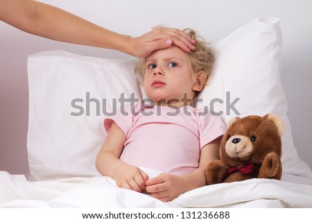 Mother checks the temperature of a sick baby - stock photo