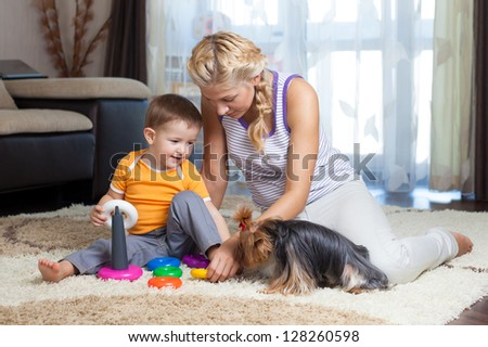 mother, child boy and pet dog playing toy together indoor - stock photo