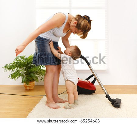 Mother cleaning the floor while she's baby is crying and wants to be picked up - stock photo