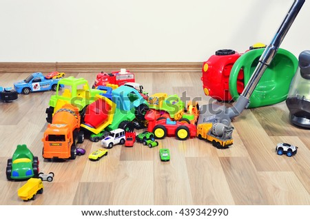 Mother cleaning the messy room full of toys. Close up on woman's hands cleaning with a vacuum cleaner. Lots of toys, many cars piled on the floor - stock photo