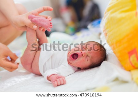 Mother cleaning up her yawning newborn baby's buttocks with wet hankies.