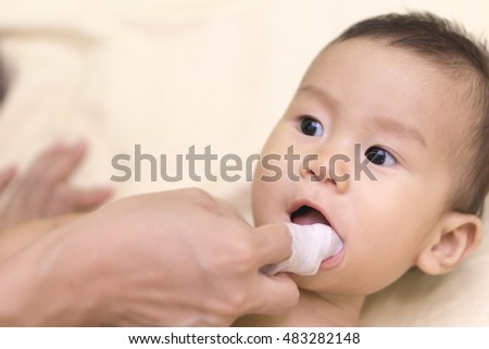 Mother cleans 8 months old baby mouth with a boiled  gauze