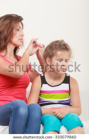 Mother combing daughter, care about hairstyle. Girl is unhappy mom pulling her hair. Important role in child life. - stock photo