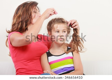 Mother combing daughter, care about hairstyle. Important role in child life. - stock photo