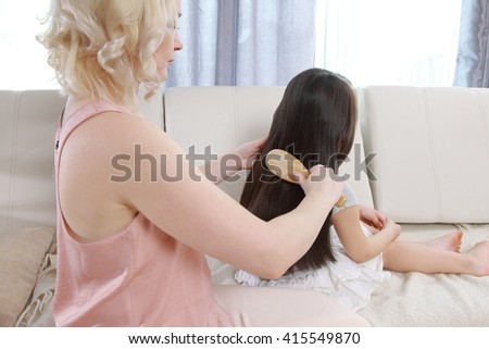 Mother combing daughter hair braids plait her