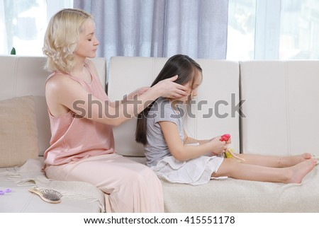 Mother combing daughter hair braids plait her   - stock photo