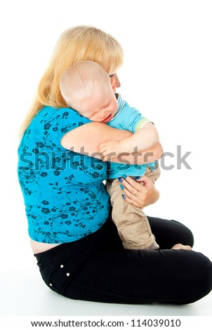 mother comforting a crying baby in her arms - stock photo