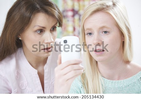Mother Comforting Daughter Being Bullied By Text Message - stock photo