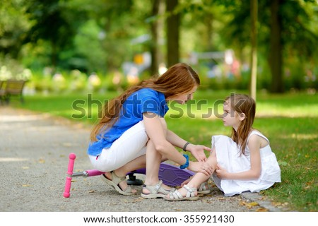 Mother comforting her daughter after she fell while riding her scooter at summer park - stock photo