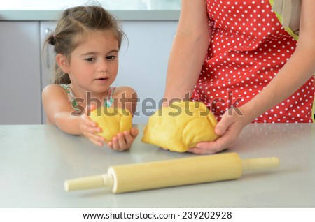 Mother compares with her child (girl age 05) knead dough in the kitchen. - stock photo
