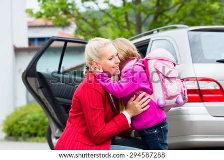 Mother consoling daughter on first day at school, the kid being a bit afraid of what may lay ahead - stock photo