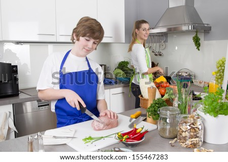 Mother cooking with her son in the kitchen