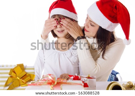 Mother covering daughter eyes with hands hiding Christmas gifts over white - stock photo
