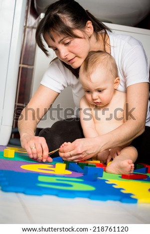 Mother cutting nails on feet of her baby - sitting on floor in bathroom - stock photo