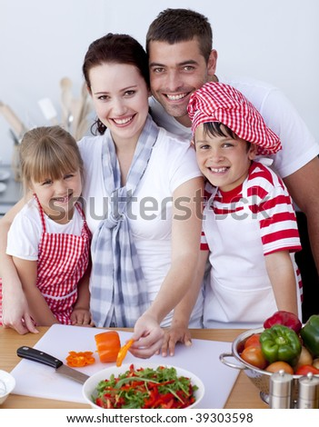 Mother cutting vegetables in kitchen with her family