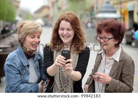 Mother, daughter and aunt looking to mobile phone and laughing