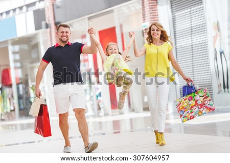 Mother, daughter and father in shopping mall. Family with shopping bags having fun smiling. Man, woman and child go on shopping.