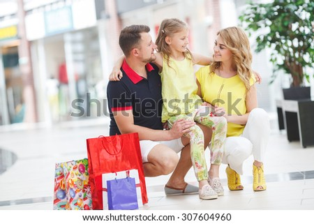 Mother, daughter and father in shopping mall. Family with shopping bags having fun smiling. Man, woman and child go on shopping.  - stock photo