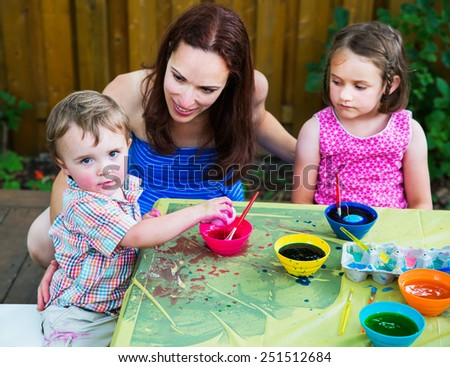 Mother, daughter and son painting and decorating eggs at a crafts table outside in a garden setting in the spring season.  The boy holds a color dyed pink Easter egg in his hand.   Part of a series.   - stock photo