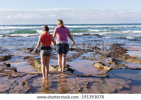 Mother Daughter Explore Beach Rock Pools Mother daughter girls on ocean beach low tide rock reefs exploring marine life - stock photo