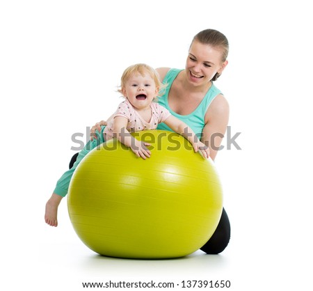 mother doing gymnastics with baby  on fitness ball - stock photo