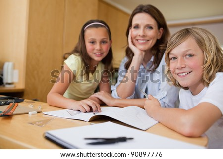 Mother doing homework with her children - stock photo