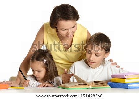 Mother doing homework with her kids - stock photo
