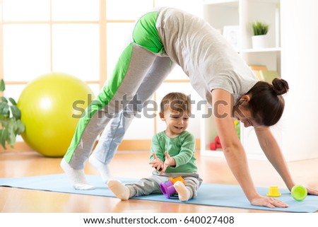 mother doing yoga or fitness exercises with son kid
