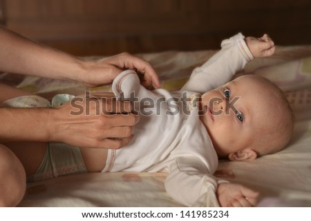 Mother dresses baby. - stock photo