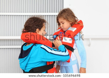 Mother dresses her daughter in orange life jacket at deck of ship - stock photo