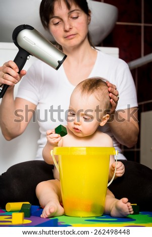 Mother drying hair of her child while baby is playing with toys - stock photo