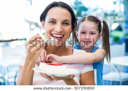 Mother eating a piece of cake with her daughter at the cafe - stock photo