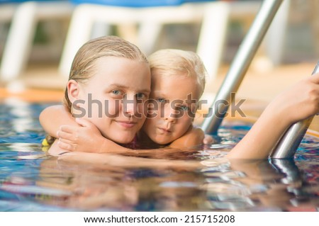 Mother embraces daughter near ladder in pool in tropical beach resort - stock photo