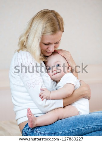 mother embracing baby boy indoors