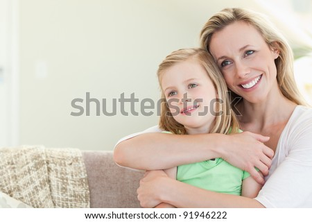Mother embracing daughter on the couch - stock photo