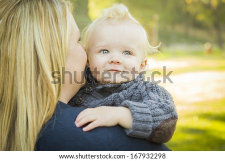 Mother Embracing Her Adorable Blonde Haired Blue Eyed Baby Boy Outdoors.  - stock photo