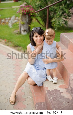 mother embracing her cute daughter on stairs - stock photo
