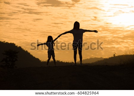 Mother encouraged Daughter outdoors at sunset, silhouette concept