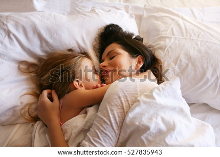 Mother enjoy in bed with her cut beautiful daughter.