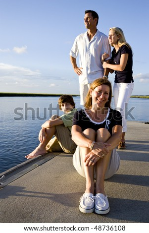 Mother enjoying sunny day on dock by water with family behind - stock photo