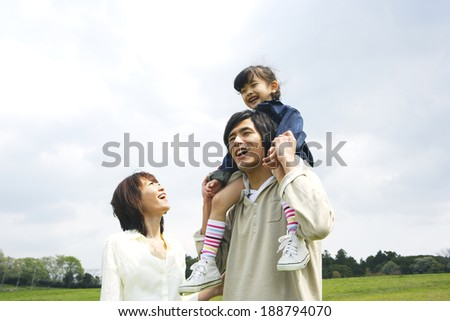 mother escorting to father with their daughter on his shoulders in prairie - stock photo