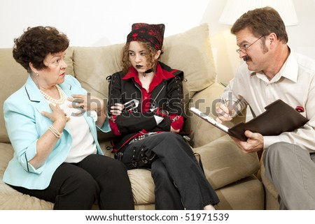 Mother explains herself to a family counselor while her rebellious teen daughter looks on. - stock photo