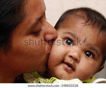 mother expressing love to daughter by kissing the child. The photo shows indian female kid smiling as her mummy embraces the toddler affectionately and kisses her - stock photo